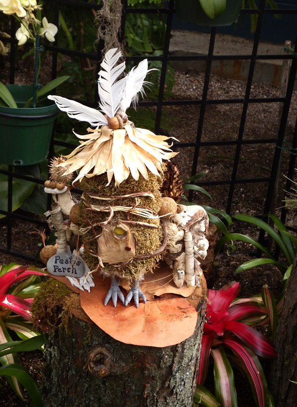 "Fairy house with feathers, ""bird feet"", leaves, moss, bark and acorns"