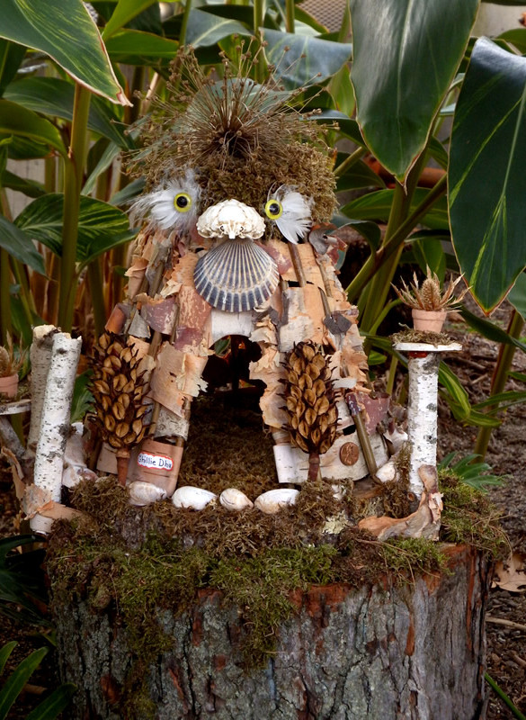 Fairy house made to look like an owl, with bark, feathers, moss and shells
