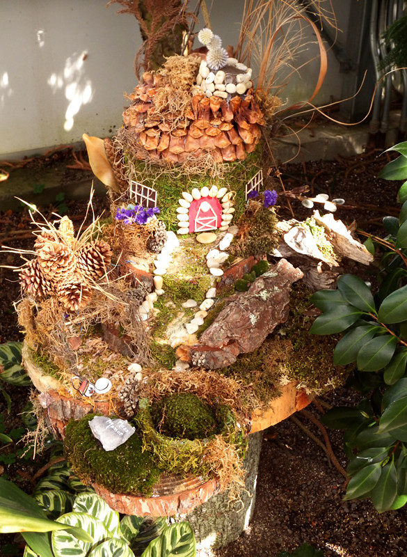 Fairy home with pine cone roof and pistachio shell doorframe and walkway