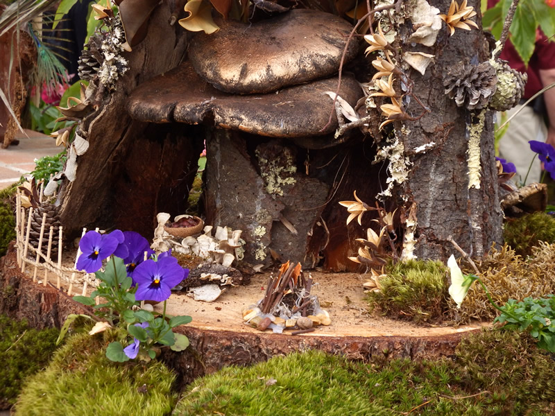 Fairy garden with mushrooms purple flowers and stick fence